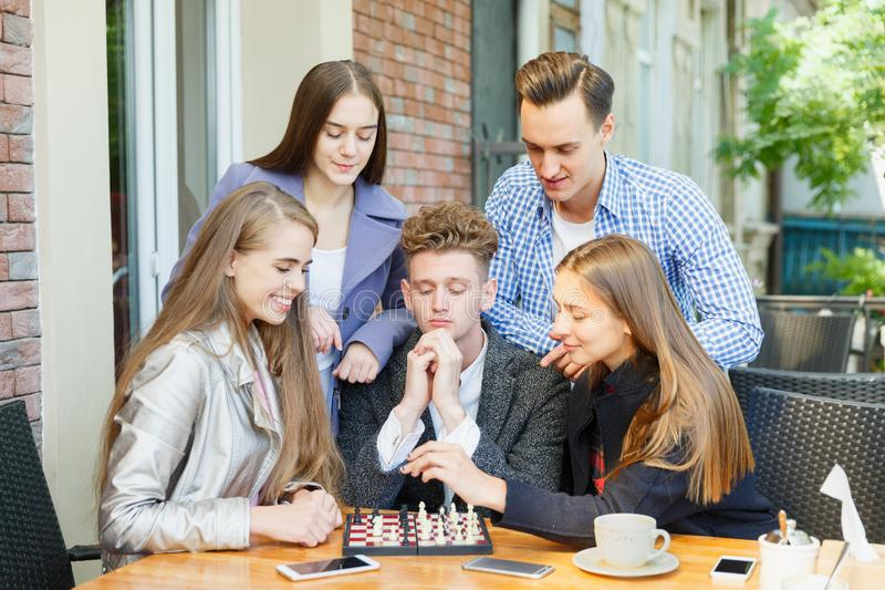 Teenage friends playing a chess game and thinking on a cafe background. Chess play concept. Five smart, gorgeous young friends playing chess on a blurred cafe stock images