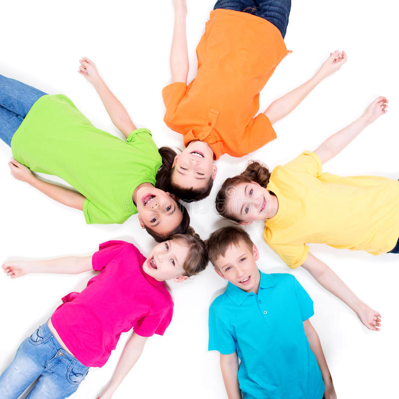 Five smiling children lying on the floor. royalty free stock photo