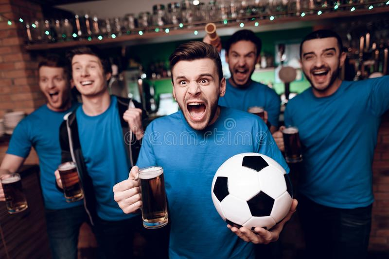 Five soccer fans drinking beer celebrating and cheering at sports bar. They are supporting blue team royalty free stock photos