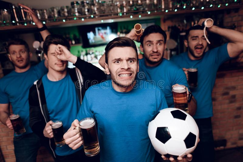 Five soccer fans drinking beer sad that their team looses at sports bar. They are supporting blue team royalty free stock images