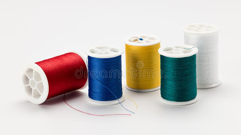 Five spools of sewing thread of different colors on a white surf stock image