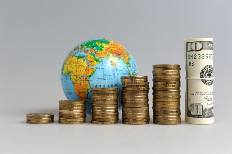 Five stacks of coins with a globe and a bundle of royalty free stock photos