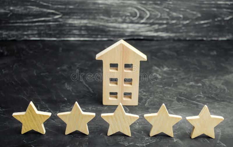 Five stars and a wooden house on a gray concrete background. The concept of the best housing, luxury apartments VIP class. The stock photo