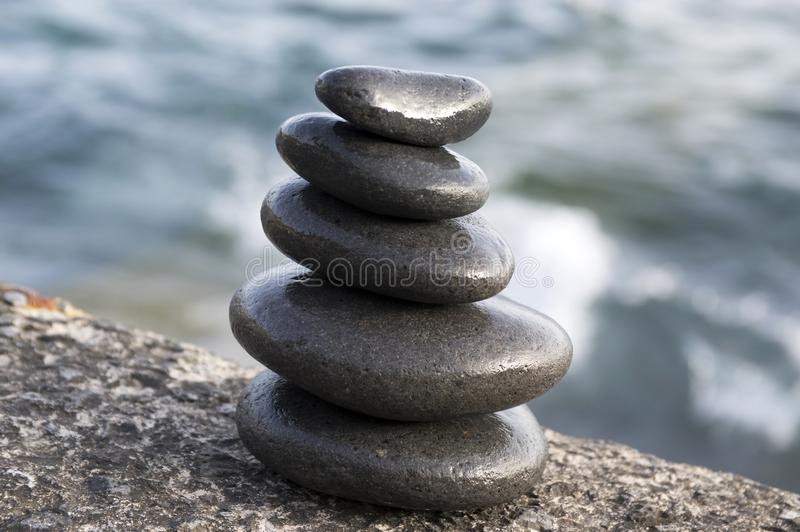 Five stones cairn tower, rock zen sculpture, black pebbles and ocean light blue background. Still life stock photos