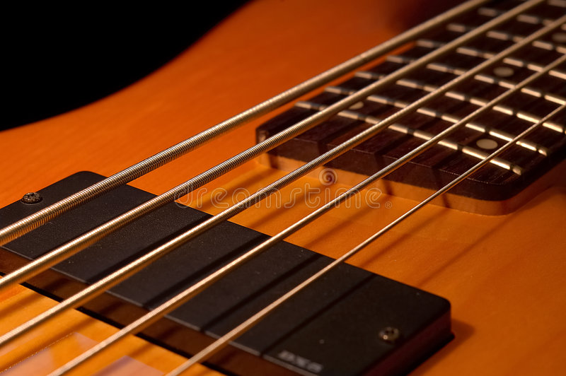 Five String Bass Angle. Angle shot of a 5 string bass in an angle with selective focus on Low B and E strings by the soapbar pickup (serial number blurred) royalty free stock images