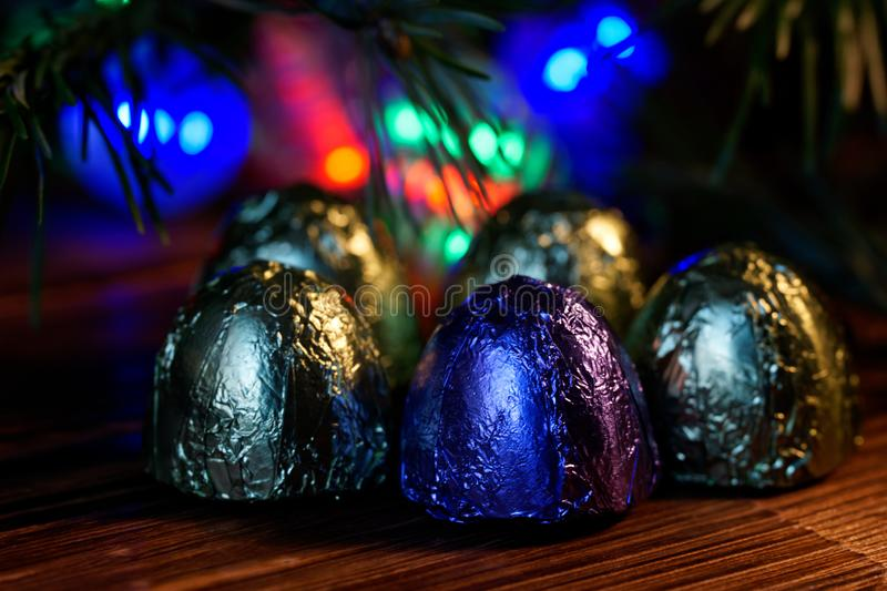 Five sweets wrapped in foil lie on a wooden surface. Background - Christmas tree and multi-colored LED lights. Night magic. Bokeh stock photos