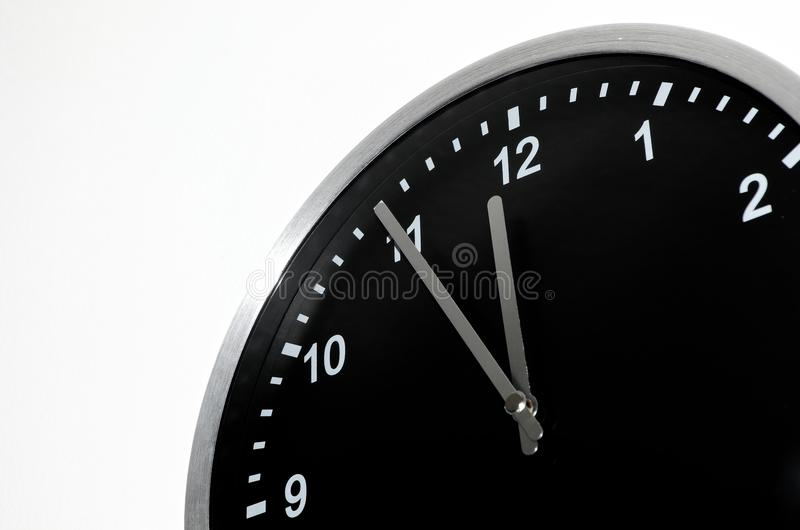 Five To Midnight setting on the black wall clock. Black wall clock with Five To Midnight setting on white background royalty free stock photos