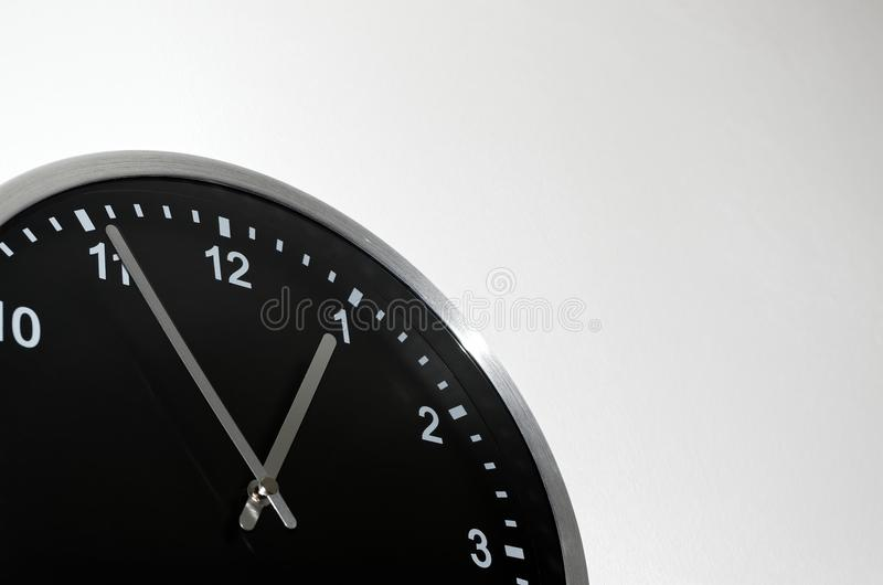 Five to one setting on the black wall clock. The black wall clock with silver colored edge on white background royalty free stock images