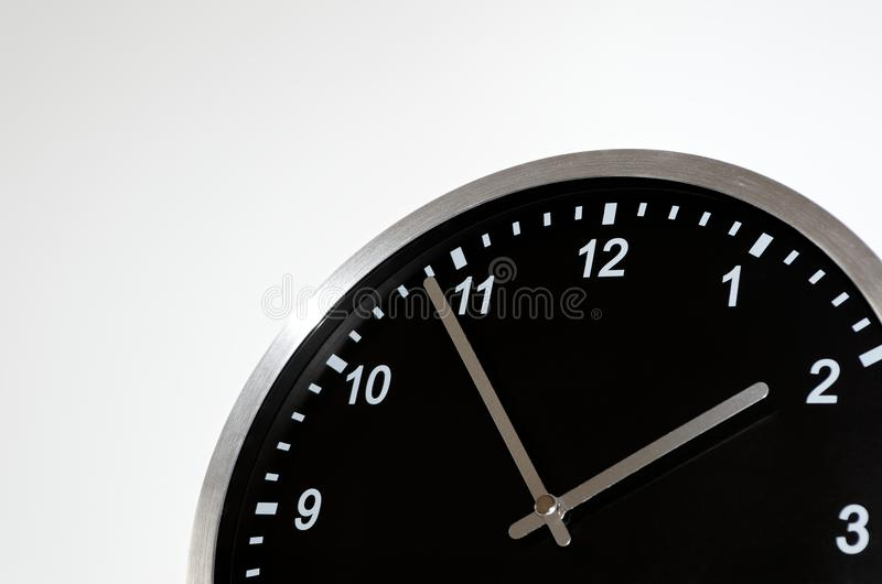 Five to two setting on the black wall clock. On white background royalty free stock images