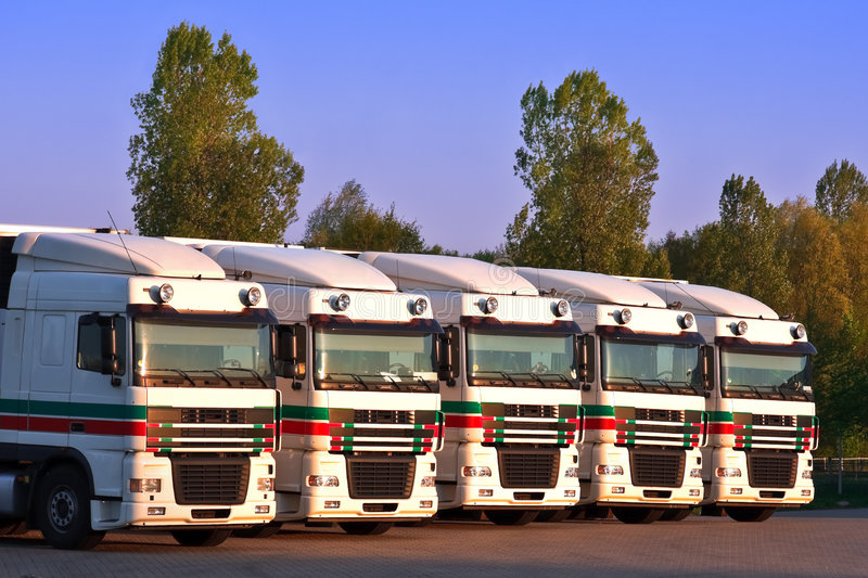 Five trucks in a row with trees and blue sky