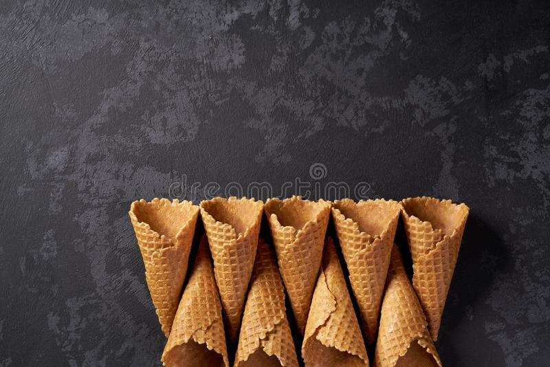 Five waffle cones waiting to be filled with ice crea, on dark background, top view. Sweet waffle cones for ice cream  concept on dark background, top view scoops stock photography