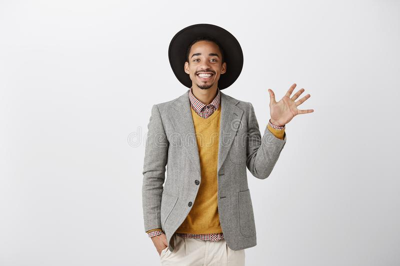Five ways to happiness. Good-looking cheerful dark-skinned male model in trendy black hat and stylish outfit raising stock photos