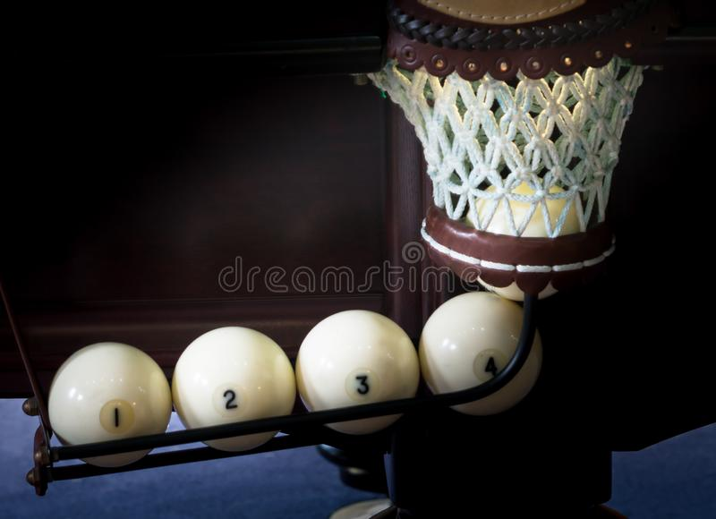 Five white billiards balls scored in the hole, the light in the hole, the background close-up royalty free stock photography