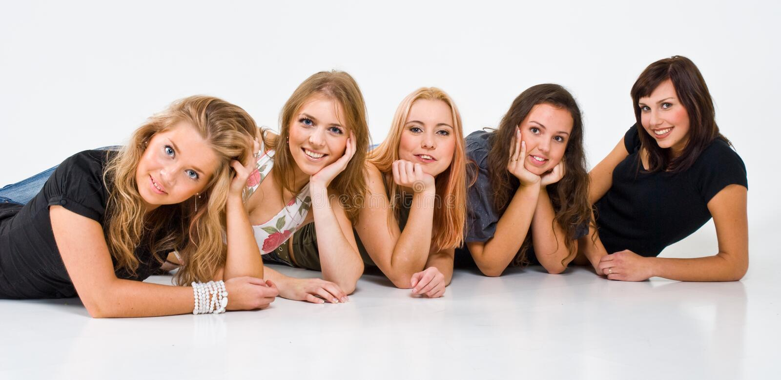 Five Women. Casual portrait of five smiling young women laying in a row, isolated on a white background. Shot in-studio
