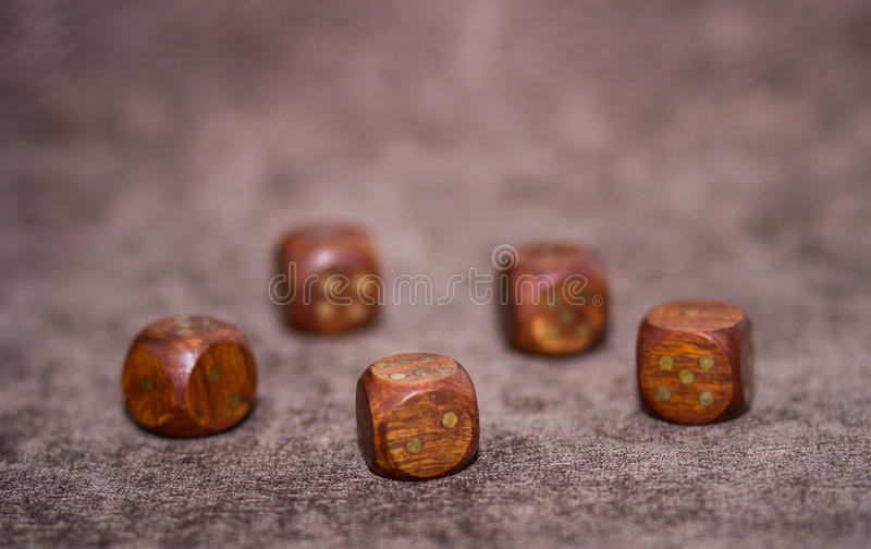 Five wooden dices on brown velvet background. Five wooden dices lying on brown velvet background royalty free stock photography