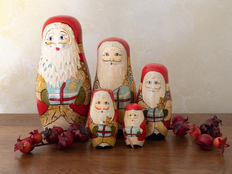 Five Wooden Santa Nesting Dolls with Berries Standing in a Group. Group of five handpainted wooden Santa Claus nesting dolls standing in a group with red berries royalty free stock photography