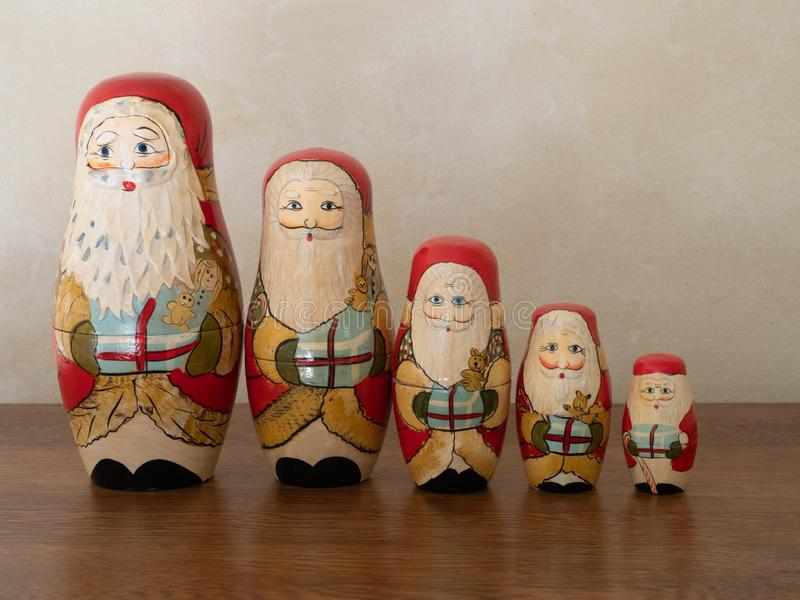 Five Wooden Santa Nesting Dolls Holding Gifts. A family of handpainted wooden Santa nesting dolls standing in a line holding gifts. Photographed on a wooden royalty free stock photo