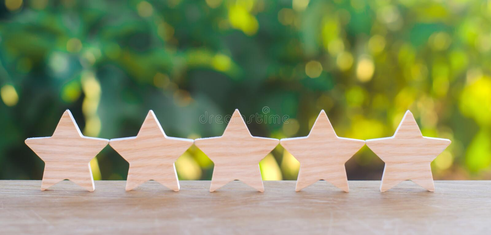 Five wooden stars. Get the fifth star. The concept of the rating of hotels and restaurants, the evaluation of critics and visitors royalty free stock images