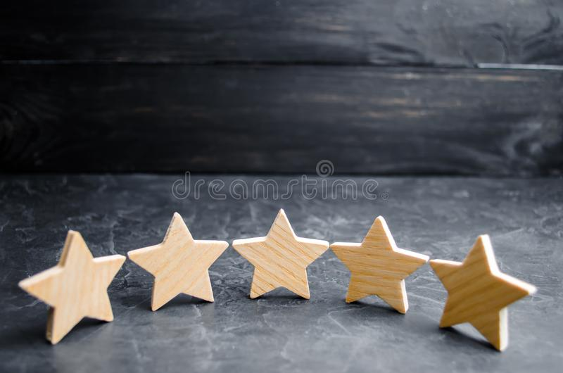 Five wooden stars. Get the fifth star. The concept of the rating of hotels and restaurants, the evaluation of critics and visitors royalty free stock photography