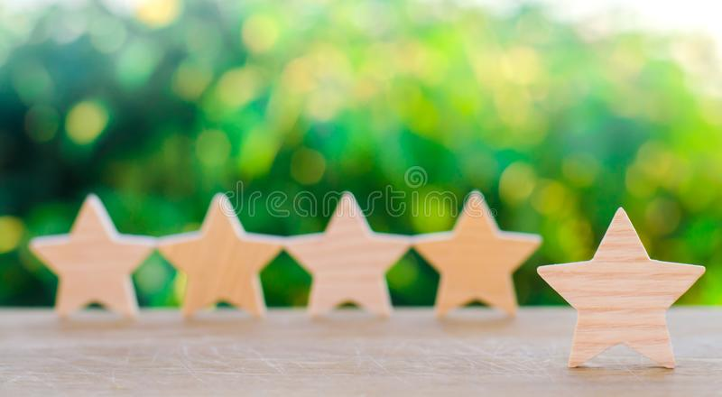 Five wooden stars. Get the fifth star. The concept of the rating of hotels and restaurants, the evaluation of critics and visitors royalty free stock image