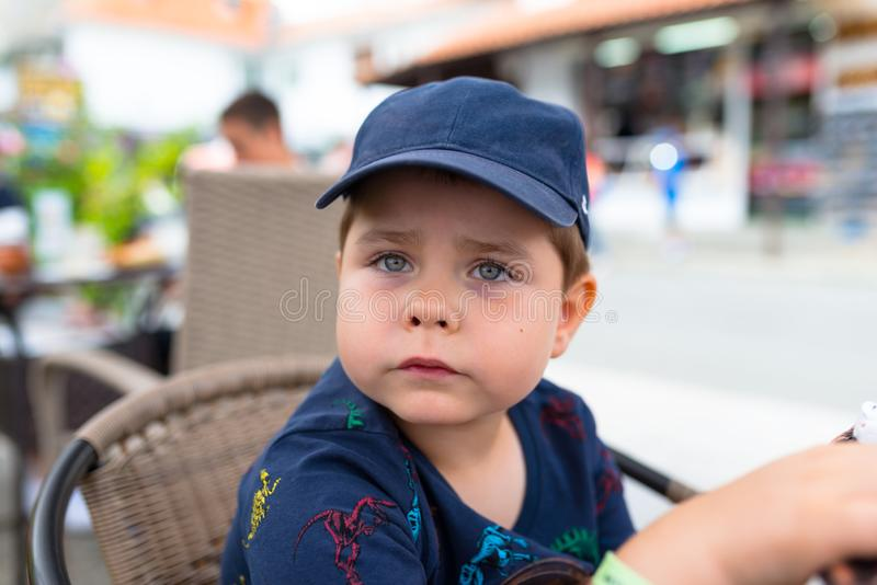 Five-year cute boy in a navy blue baseball cap sitting on a wicker chair outside in a restaurant. royalty free stock image