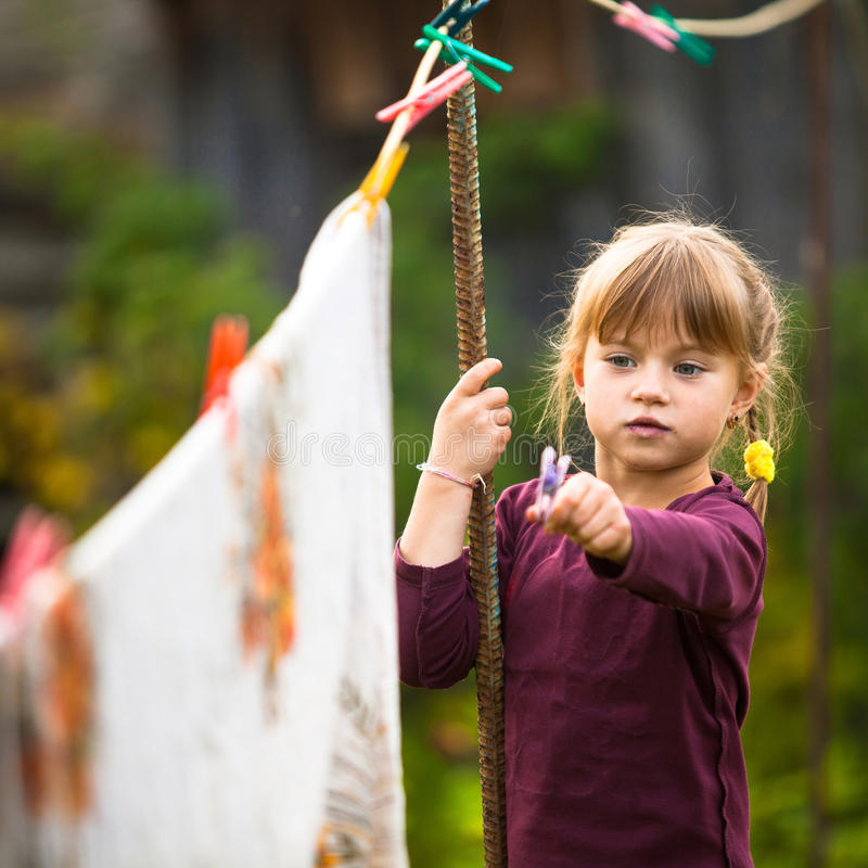 Five-year flicka med den utomhus- klädnypan royaltyfri fotografi