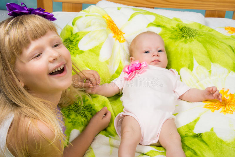 Five-year girl joyfully laughs while holding the handle of a newborn baby. The five-year daughter sitting in the crib on the bed lying on her back a two-month stock image