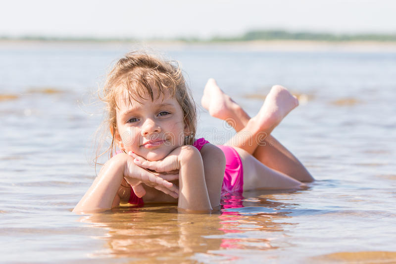 Five-year girl lies in water in shallows of the river stock photos