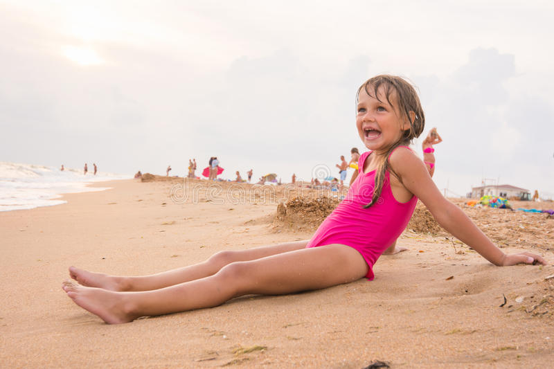 Five-year girl sits on beach in the evening sea coast on a cloudy day stock photo