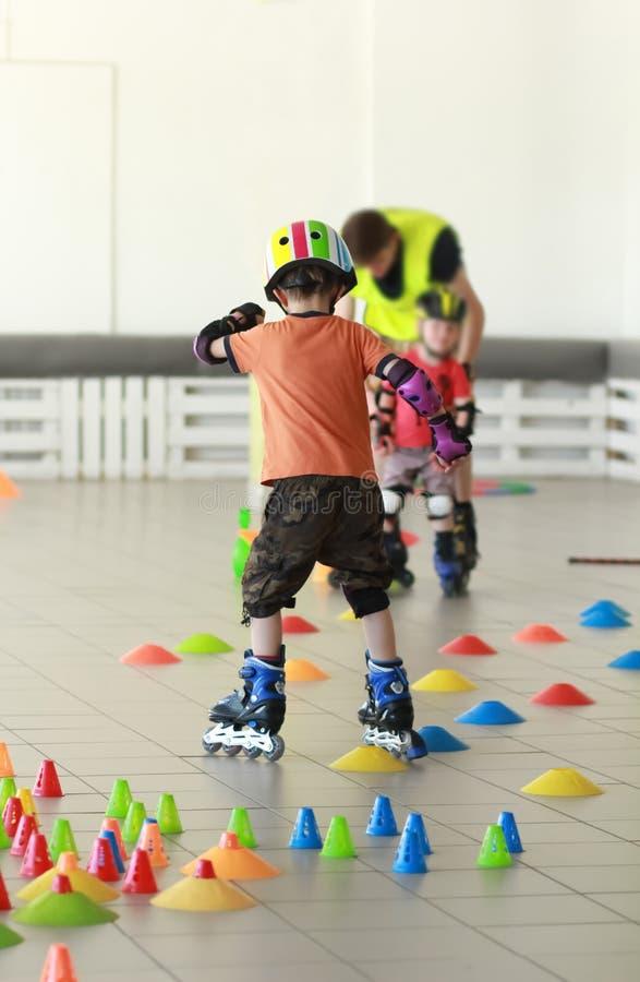 Five year old boy in a helmet learn freestyle rollerblade slalom stock image