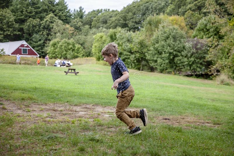 Five year old boy running outside on farm royalty free stock photo