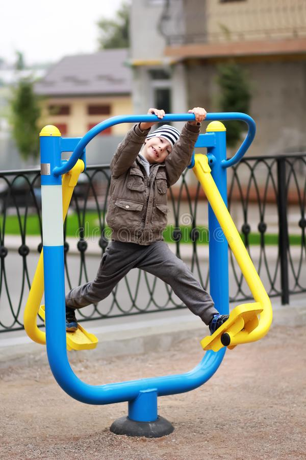Five year old boy working out in the street, in the outdoor gym on the playground. Five year old boy working out in the street, in the outdoor gym in the yard on royalty free stock images