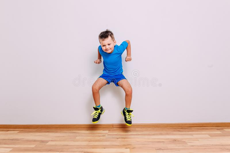 A five-year-old child in clean basketball sneakers and sports uniform jumps high on a white background royalty free stock photo