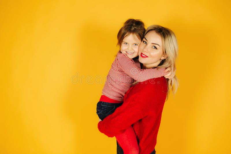 Five year old girl on mothers hand. Little girl with her blond hair mom. Yellow background royalty free stock photos