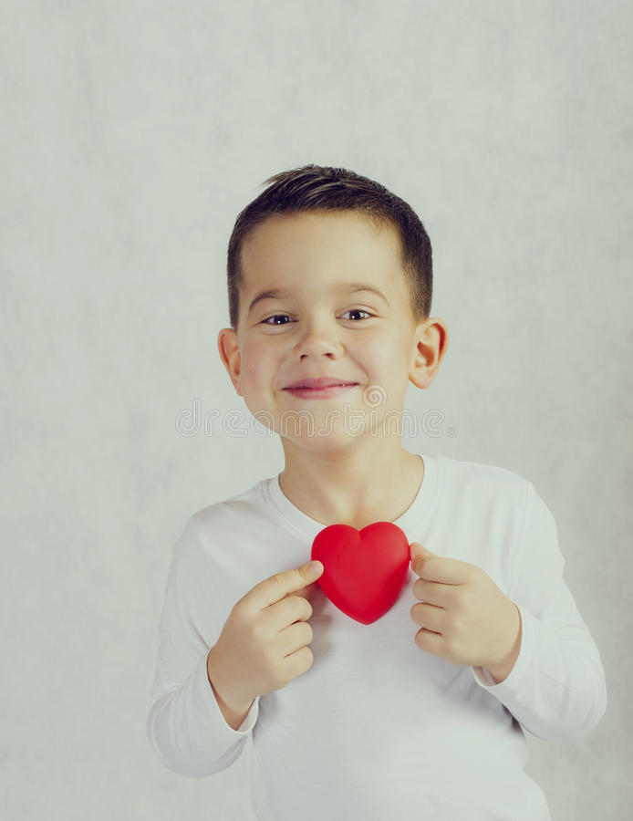 Five year old smiling boy holding a red heart figurine stock photo