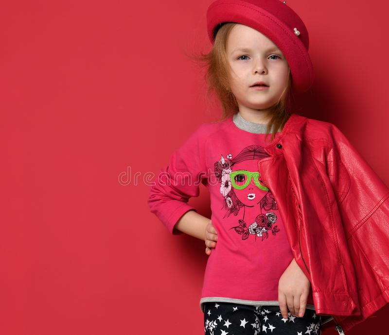 Five years old baby girl child kid posing in red leather jacket and hat on red royalty free stock images