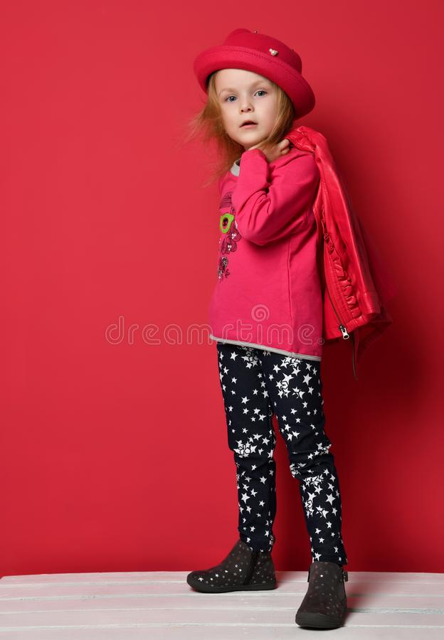 Five years old baby girl child kid posing in red leather jacket and hat on red stock photography