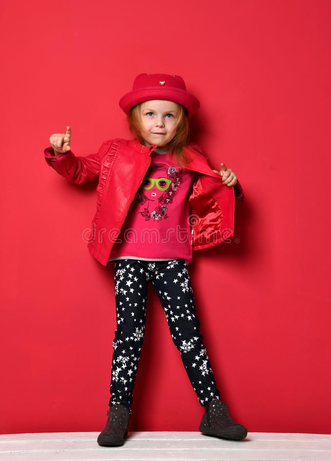 Five years old baby girl child kid posing in red leather jacket and hat pointing finger up on red royalty free stock photo