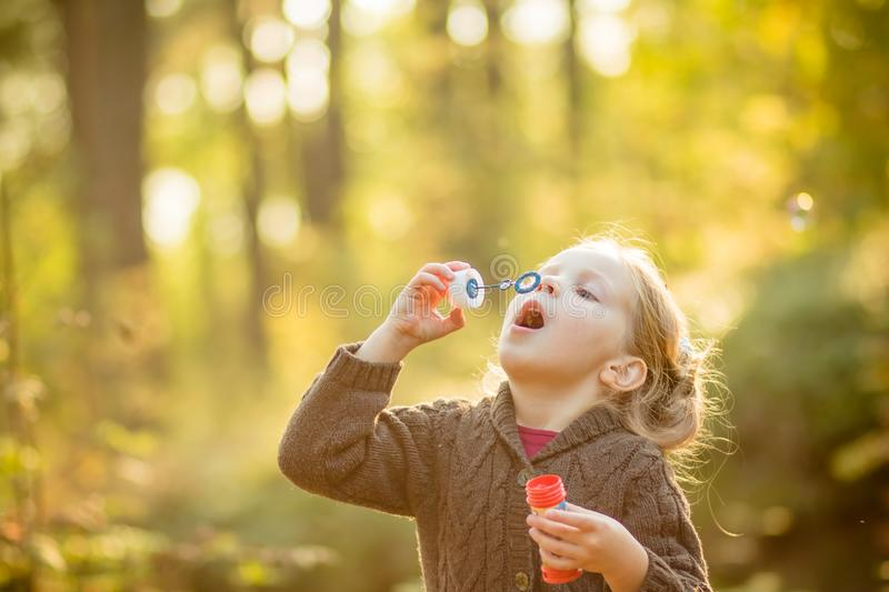 Five years old caucasian child girl blowing soap bubbles outdoor at sunset - happy carefree childhood.Fall seasom stock photo