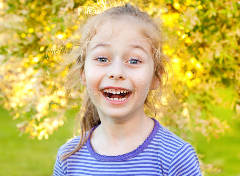 Five years old caucasian child girl laughing in the garden. Portrait of happy laughing five years old caucasian child girl in the garden during summer - sunset stock photo