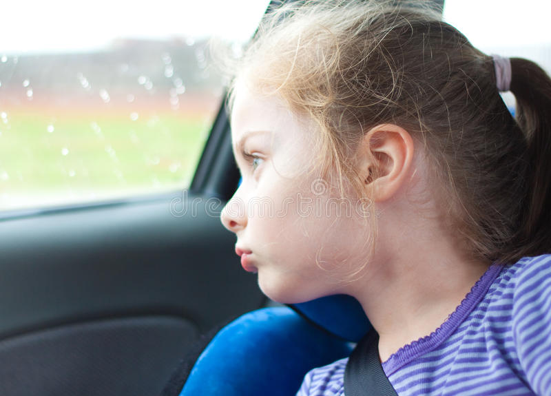 Five years old child girl traveling in a car seat. Five years old blond caucasian child girl looking out the window while traveling in a car seat royalty free stock photo