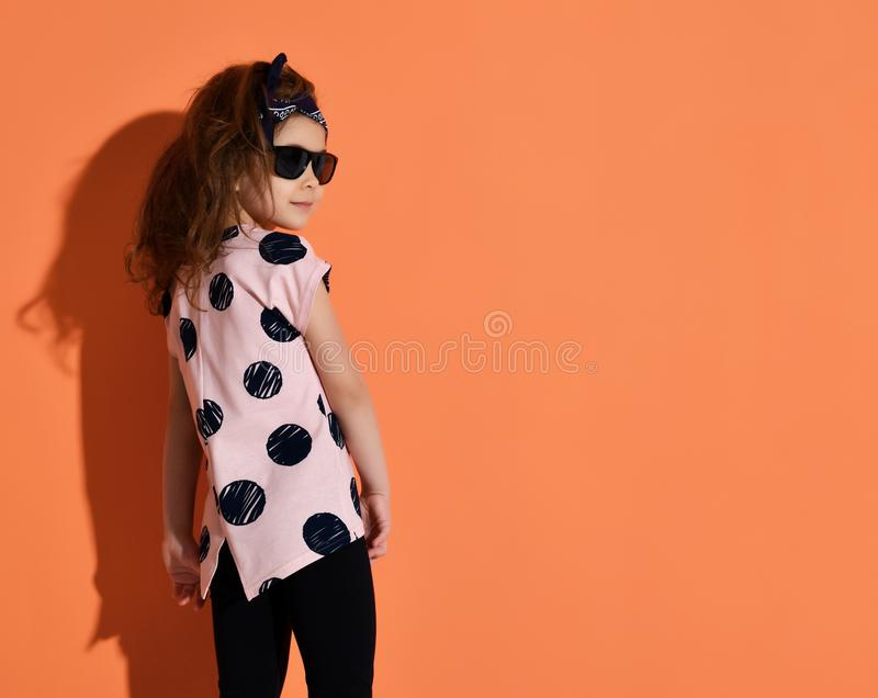 Five years old girl kid posing in summer shirt and sunglasses on orange background stock photos