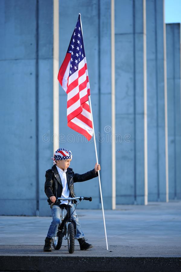 A five years old smiling boy is sitting on a bicycle and holding american flag on a stick stock photos
