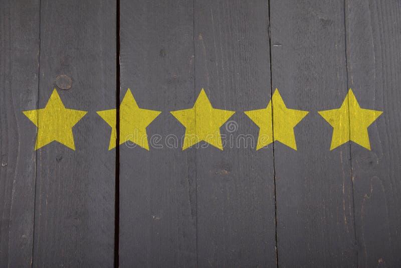 Five yellow ranking stars on wooden background. Five yellow ranking stars on black wooden background stock photo