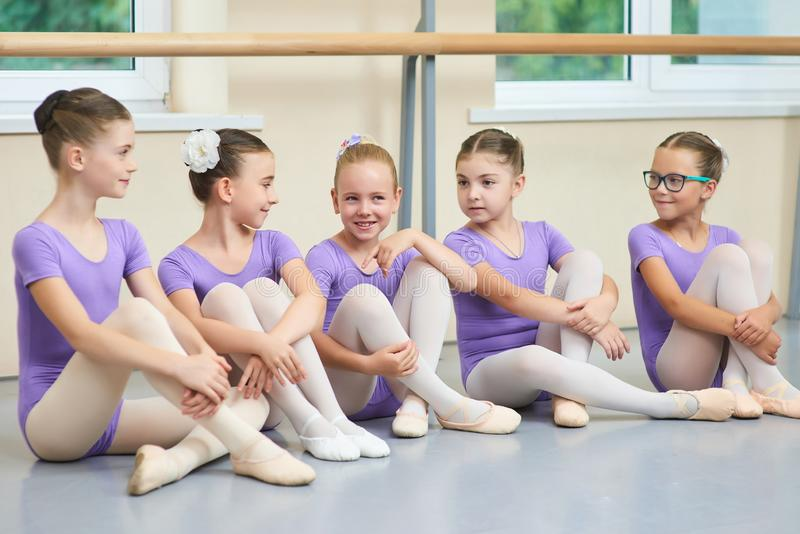 Five young ballerinas sitting on the floor. stock photos