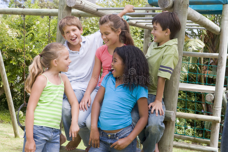 Five young friends at a playground smiling stock image