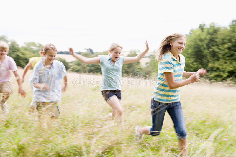 Five young friends running in a field smiling stock photography