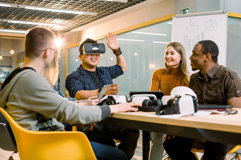 Five young funny people sitting at the table in front of each other, one man is using virtual reality goggles. VR royalty free stock photo