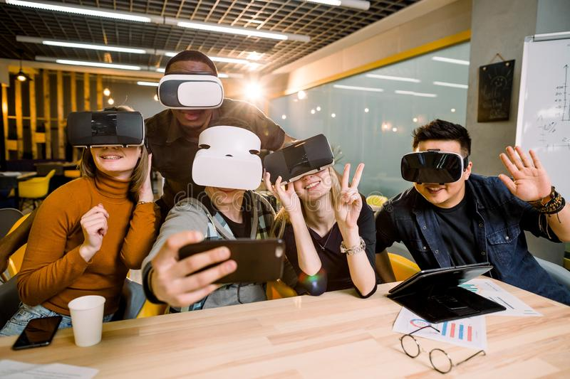 Five young funny people sitting at the table in front of each other, using virtual reality goggles, having fun and stock photos