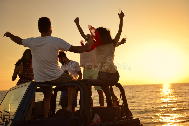 Five young people having fun in convertible car at the beach at sunset. royalty free stock image